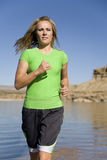 Woman at lake running. A woman running in the lake water with a beautiful back drop of rocks and mountains Stock Photography
