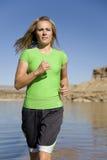 Woman at lake running Stock Photography