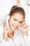 Woman on land line call, smiling at camera. Portrait of office girl on land line call, smiling at camera Stock Images