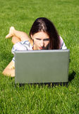 Woman with laptop. Young beautiful woman, lying on the grass with the laptop Royalty Free Stock Photo