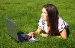 Woman with laptop. Young beautiful woman, lying on the grass with the laptop Royalty Free Stock Photography