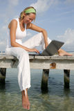 Woman and Laptop. Woman on a tropical jetty with a laptop Royalty Free Stock Photography