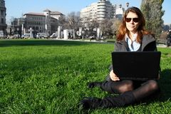 Woman with laptop. Beautiful young businesswoman wearing sunglasses, sitting on a grass with her laptop Stock Photography