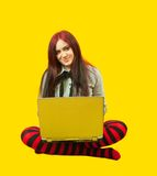 Woman with a laptop. Casual woman with laptop  over a yellow  background Stock Photos