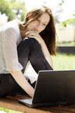 Woman with a laptop. Pretty young woman with a laptop at park Royalty Free Stock Photo