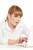 Woman with laptop. Young shocked woman with laptop surfing internet on laptop over white Stock Photo