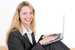 A woman with a laptop. A smiling woman sitting on the floor with a silver laptop on her knees Stock Photography