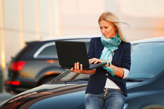 Business woman with laptop at the car Stock Image