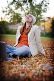 Woman with laptop 24. Woman dressed in fall clothing sits in the leaves with her head looking up towards the sky Royalty Free Stock Image