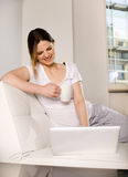 Woman using laptop on sofa Royalty Free Stock Photography