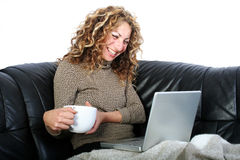 Woman with Laptop. Digital photo of a woman sitting at the sofa and surfing Royalty Free Stock Photography