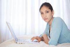 Woman on laptop. Woman lying on bed in front of laptop Stock Photo