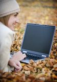 Woman and laptop. Young woman on her laptop in the fall Royalty Free Stock Photo