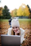Woman and laptop. Young woman having fun on her computer in the fall Royalty Free Stock Image
