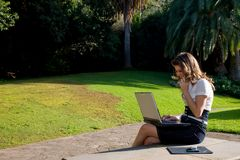 Woman with laptop. Young woman with laptop and phone working at outdoor Royalty Free Stock Photo