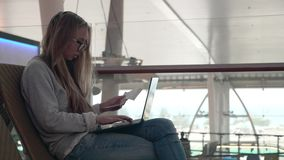 Woman With Laptop at the Airport. Young woman working with laptop in airport terminal and waiting for flight. Young girl booking tickets online stock video