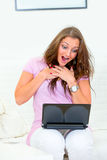 Woman with laptop amazedly looking at monitor. Pretty woman sitting on sofa with laptop and amazedly looking at monitor Royalty Free Stock Photos