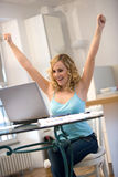 Woman at laptop with arms up Stock Photo