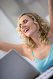 Woman at laptop with arms up Stock Photography