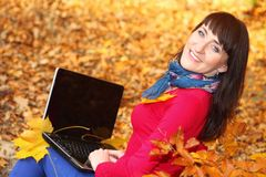 Woman with laptop in autumn park Stock Image