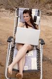Woman with laptop on the beach Stock Image