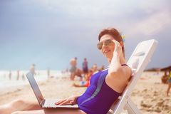 Woman with laptop on the beach Stock Photo