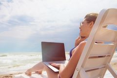 Woman with laptop on the beach Royalty Free Stock Image