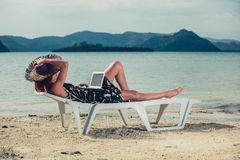 Woman with laptop on beach Royalty Free Stock Photography