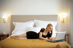 Woman with laptop on bed Royalty Free Stock Photos