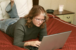 Woman on laptop in bed Stock Photography