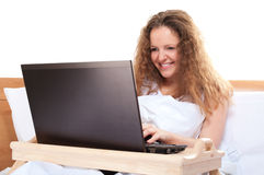 Woman with laptop in bed Royalty Free Stock Photo