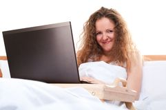 Woman with laptop in bed Royalty Free Stock Images