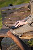 Woman with laptop on bench Stock Photography