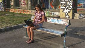 Woman with laptop on the bench in the park. Young woman working with a laptop sitting on a bench with graffiti in the city park stock video footage
