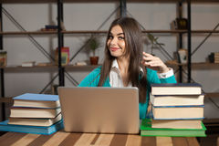Woman with laptop and books. Woman with lots of books and laptop is sitting at the table Royalty Free Stock Photography