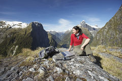 Woman With Laptop On Boulder Against Mountains Stock Photos