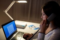 Woman with laptop calling on phone at night office. Business, overwork, deadline and people concept - woman typing on laptop and calling on phone at night office Royalty Free Stock Photography