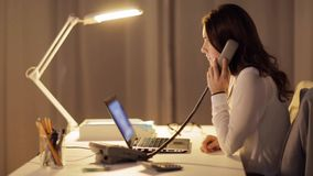Woman with laptop calling on phone at night office. Business, overwork, deadline and people concept - woman typing on laptop calling on phone at night office stock footage