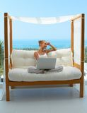Woman with laptop on canopied seat. Beautiful woman sitting on a canopied seat on her patio, resting her head on her hand as she takes a break from working on Stock Photo
