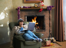 Woman with laptop and Christmas gifts by the fireplace. In the armchair Royalty Free Stock Photo