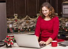 Woman with laptop in Christmas kitchen Stock Photo