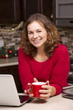 Woman with laptop in Christmas kitchen Royalty Free Stock Photography