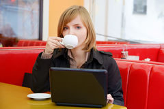 Woman with laptop and coffee Stock Images