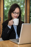 Woman with laptop and coffee Stock Image
