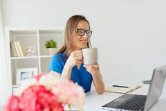 Woman with laptop and coffee at home or office. Business, freelance, people and technology concept - happy smiling woman with laptop computer drinking coffee at Stock Image