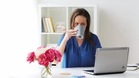 Woman with laptop and coffee at home or office