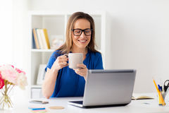 Woman with laptop and coffee at home or office. Business, freelance, people and technology concept - happy smiling woman with laptop computer drinking coffee at Stock Photography