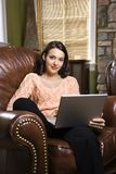 Woman with laptop computer. Caucasian/Hispanic young woman sitting in leather chair with laptop looking at viewer Stock Photo