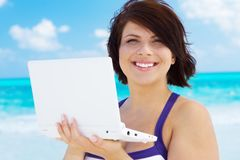 Woman with laptop computer on the beach Stock Image