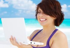 Woman with laptop computer on the beach. Lovely woman with laptop computer on the beach Royalty Free Stock Image